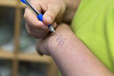 Bild zeigt Person die eine Notiz auf Ihren Arm schreibt, stellvertretend als Aufgabenerinnerung
