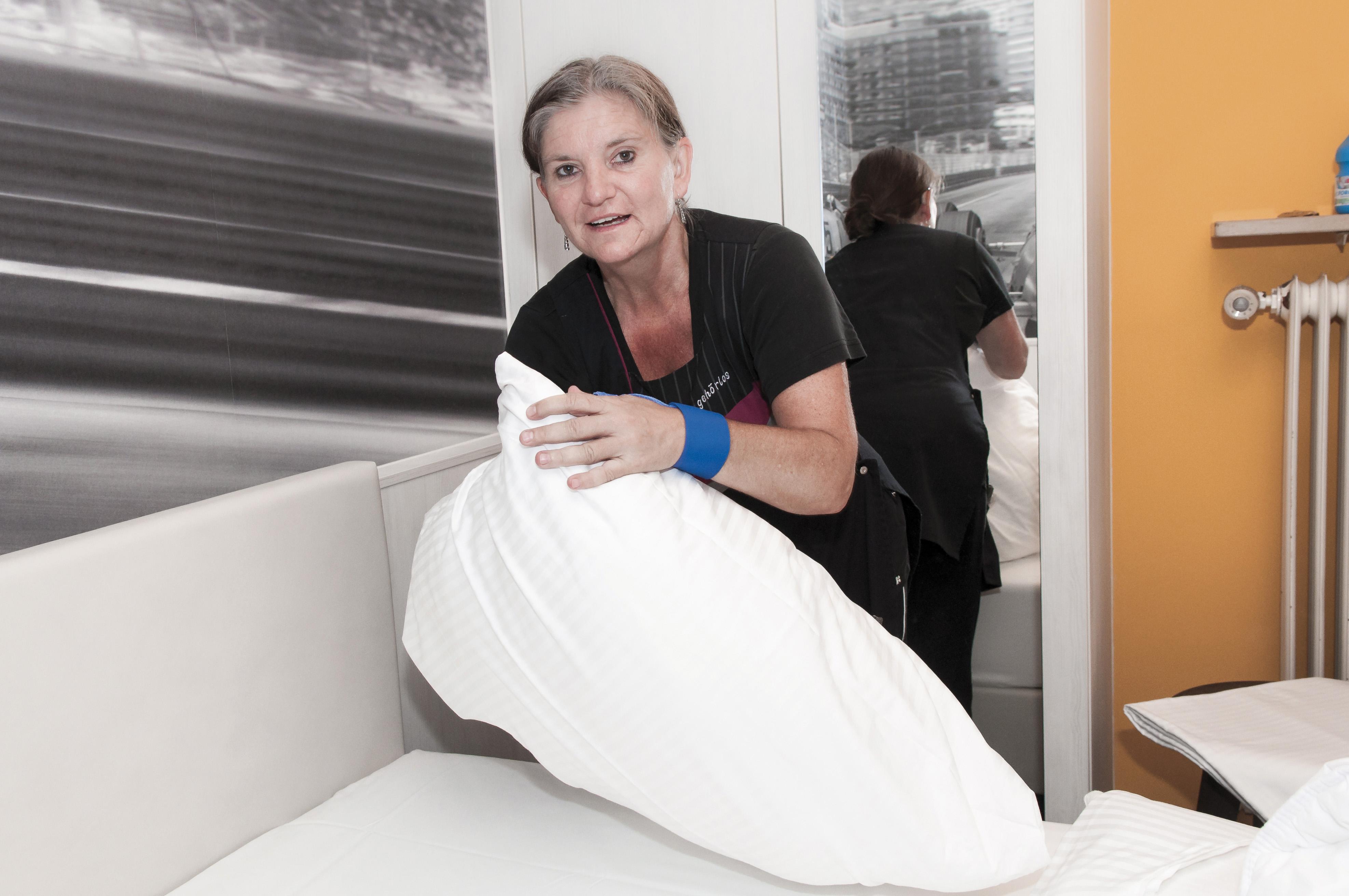 Frau in Hotelzimmer beim Kissen beziehen