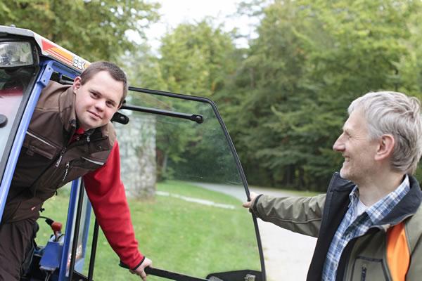 Bild zeigt Mitarbeiter mit Behinderung bei seiner Arbeit zusammen mit seinem zufriedenen Arbeitgeber.