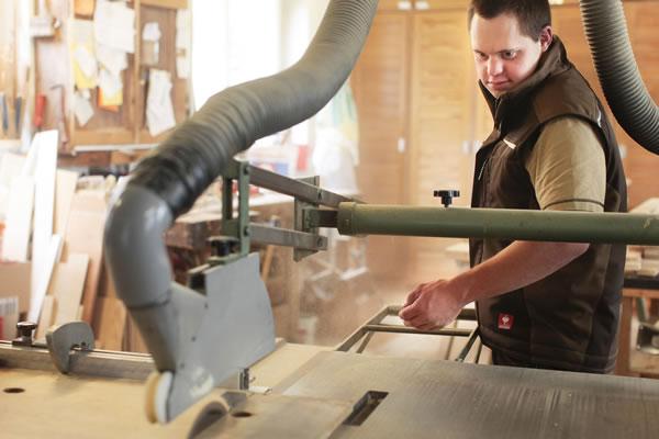 Bild zeigt Mitarbeiter mit Behinderung bei der Arbeit an einer großen Sägemaschine.