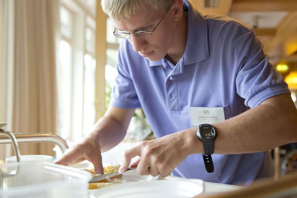 Bild zeigt Mitarbeiter mit Handicap bei der täglichen Arbeit